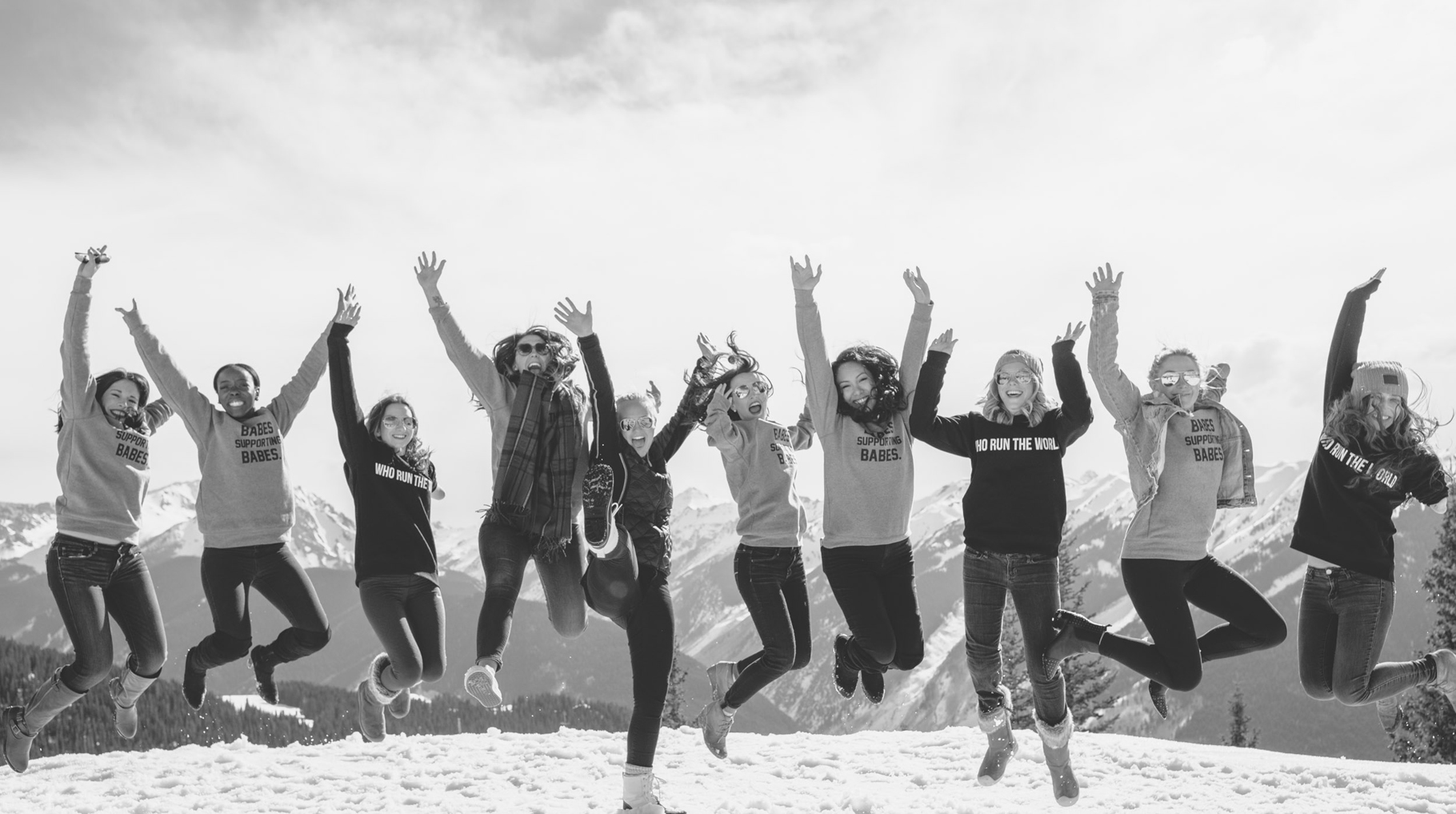 Group of nominees jumping for a picture on top of a snowy mountain